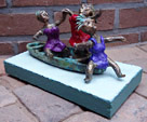 Painted bronze statue Pleasure Boating by Twan de Vos, three women dancing, singing and having fun on a boat